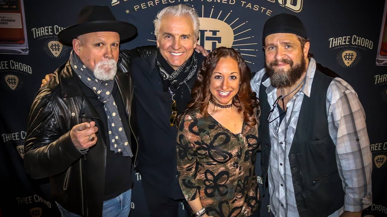 Neil Giraldo and three other musicians in front of a black background. musicians, music, Next Avenue, Three Chord Bourbon