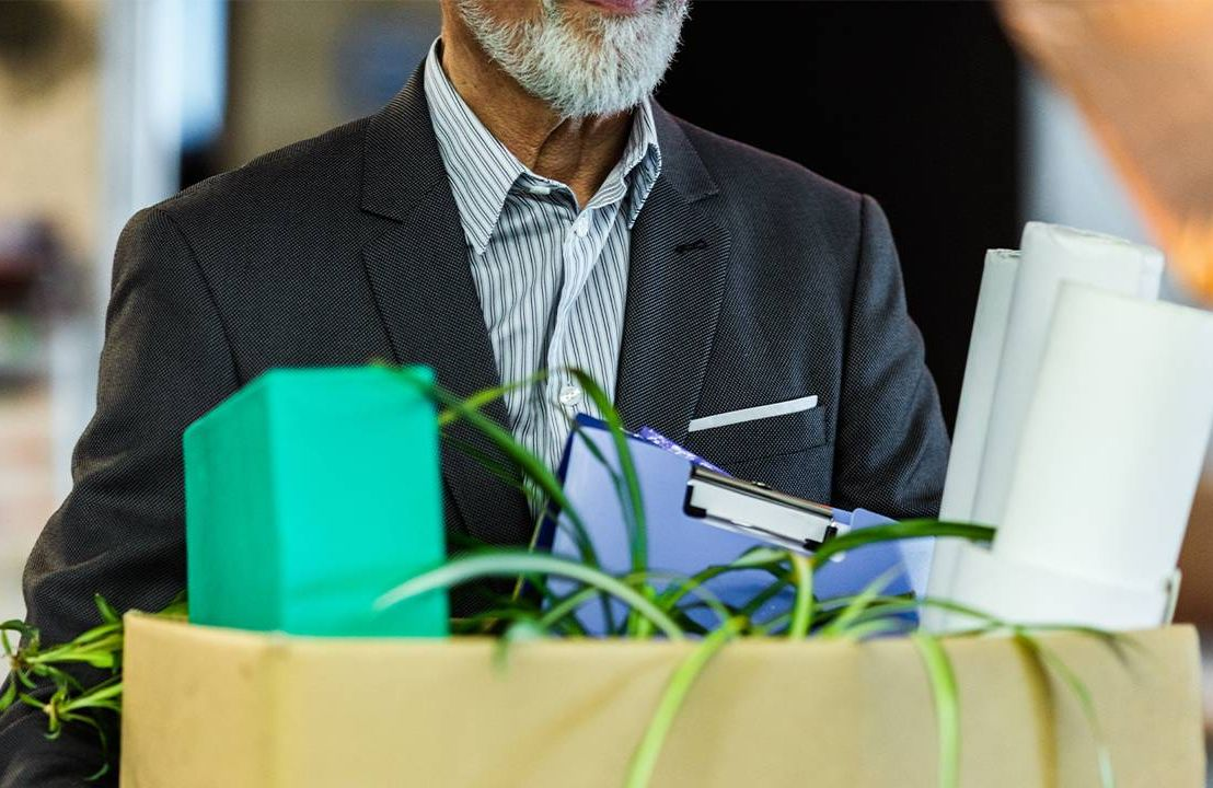 An older worker holding a box of things from his desk. Next Avenue, the big quit, older workers