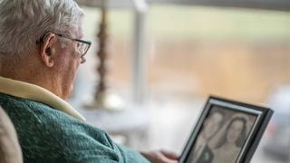 Older man looking at wedding photo. Next Avenue, Grief, spouse