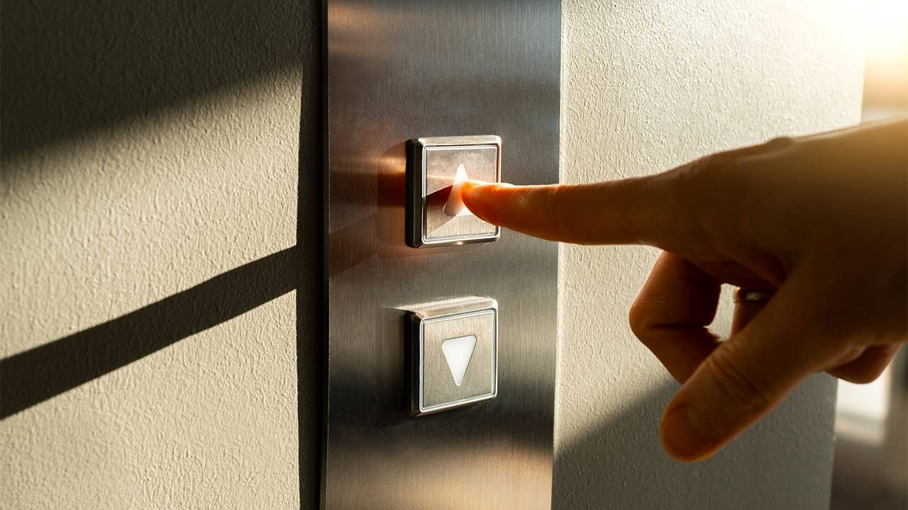 A person's finger pushing an elevator button. Retirement, pitch, Next Avenue