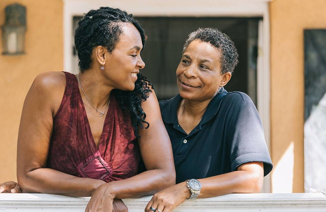 An LGBTQ couple smiling at eachother, LGBTQ housing, Next Avenue