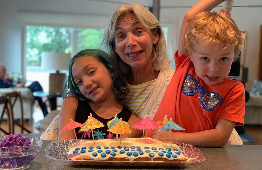 Freddi Greenberg and her grandchildren smiling in front of a cake. Next Avenue, grandparents, grandmother, grandchildren