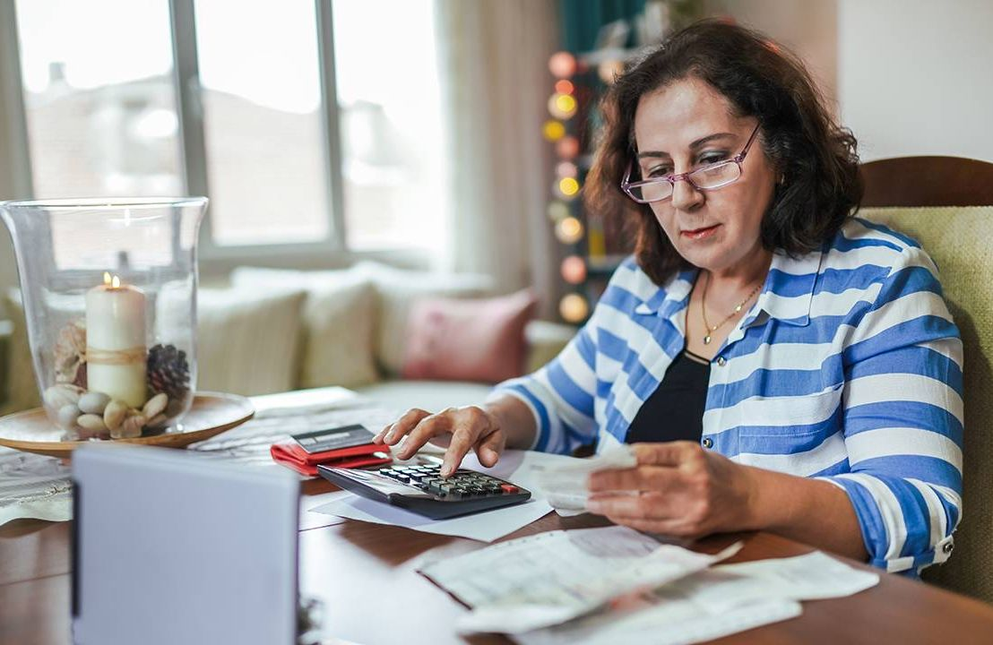 A woman sitting down to calculate her finances. Retirement savings, Next Avenue