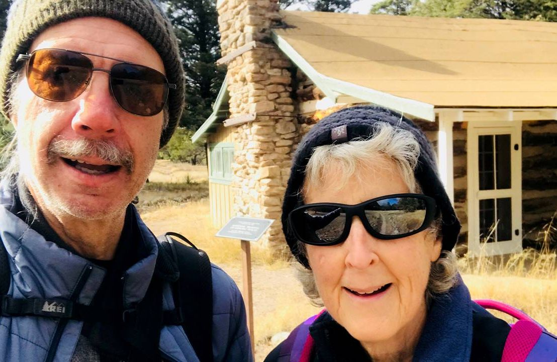 An older couple smiling in front of a log cabin. Retirement, rural, Next Avenue, health care