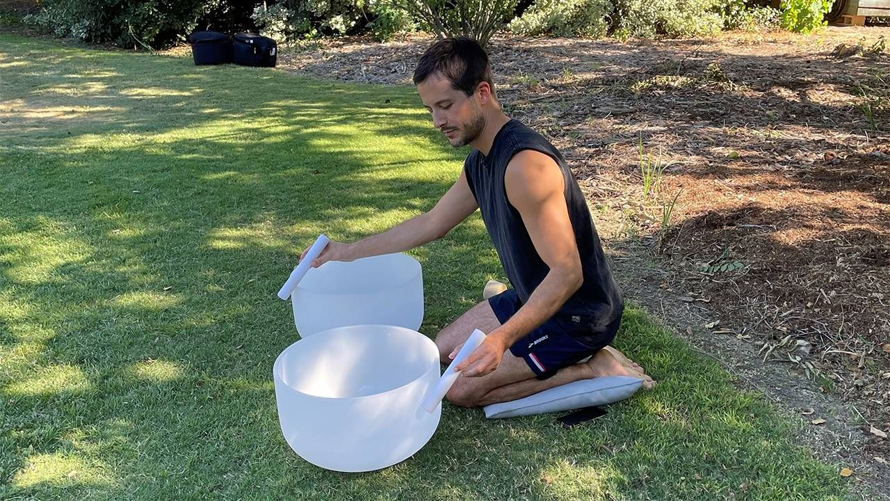 A man kneeling on a pillow playing the singing bowls for a sound bath. Next Avenue, stress