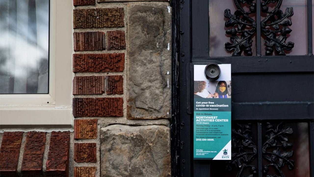 A door knocker hanging on a door knob to get the word out about getting the COVID-19 vaccine. Vaccine hesitancy, Next Avenue