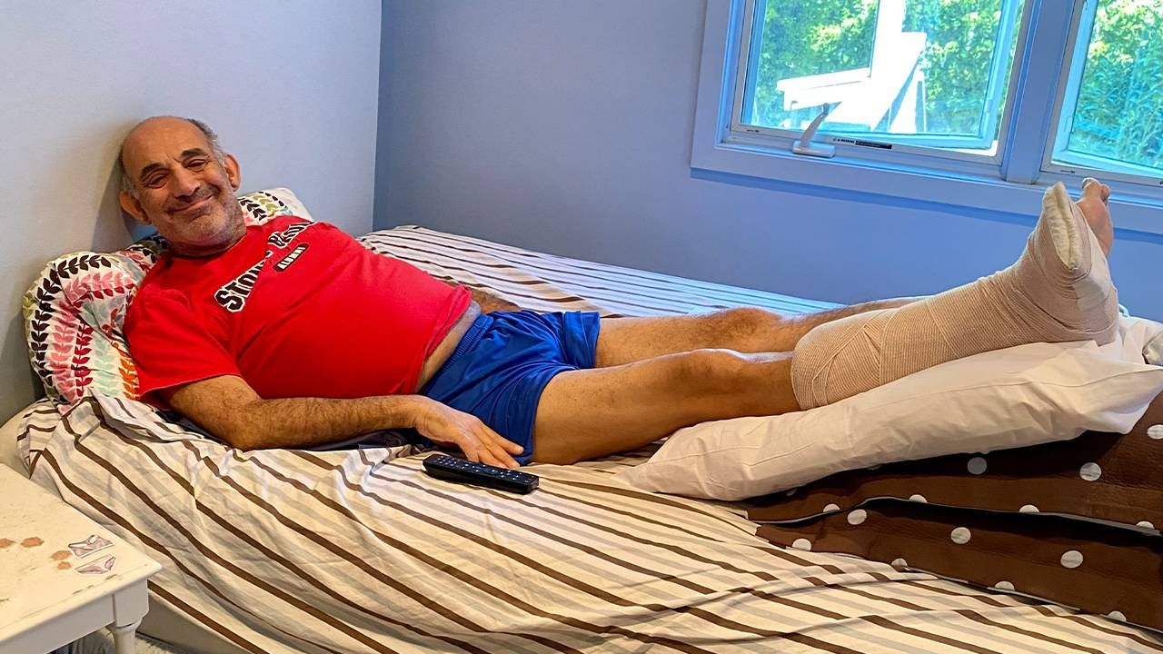 The author laid up in bed with his foot in a cast. Next Avenue, surgery recovery