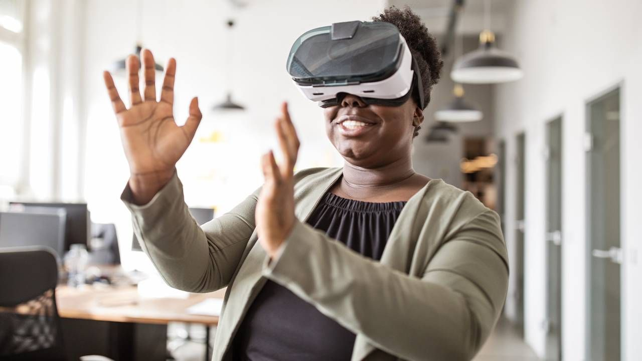 A woman standing up wearing a VR headset. Next Avenue, virtual reality