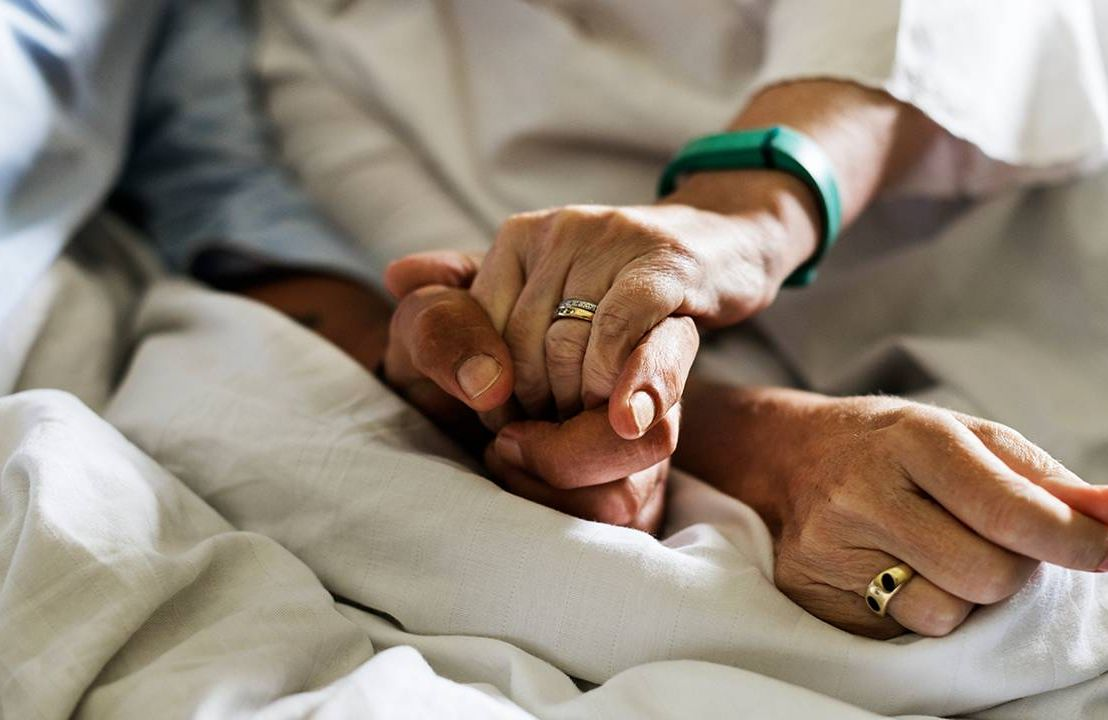 A wife holding hands with her husband in hospice. Next Avenue, VSED, Voluntarily Stopping Eating and Drinking, end of life