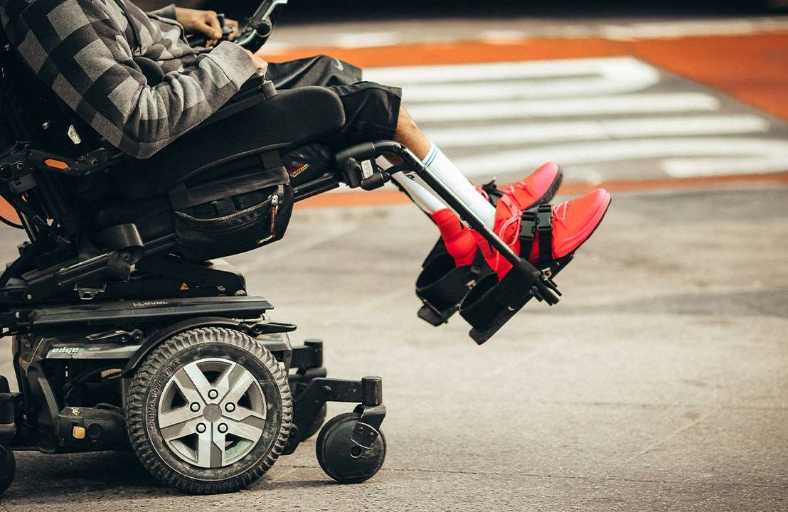 A closeup of a motorized wheelchair with a person sitting in it. Next Avenue, wheelchair damage, airport