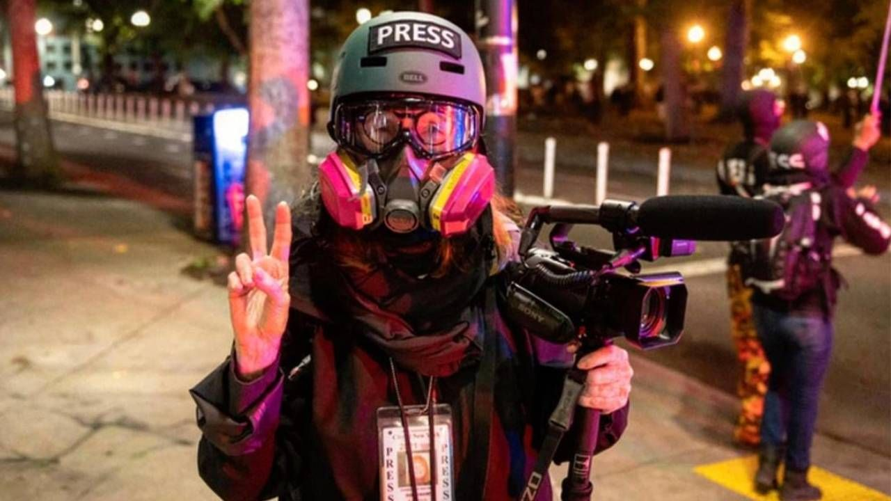 Sandi Bachom wearing a helmet and gas mask while covering protests. Next Avenue, documentary filmmaker