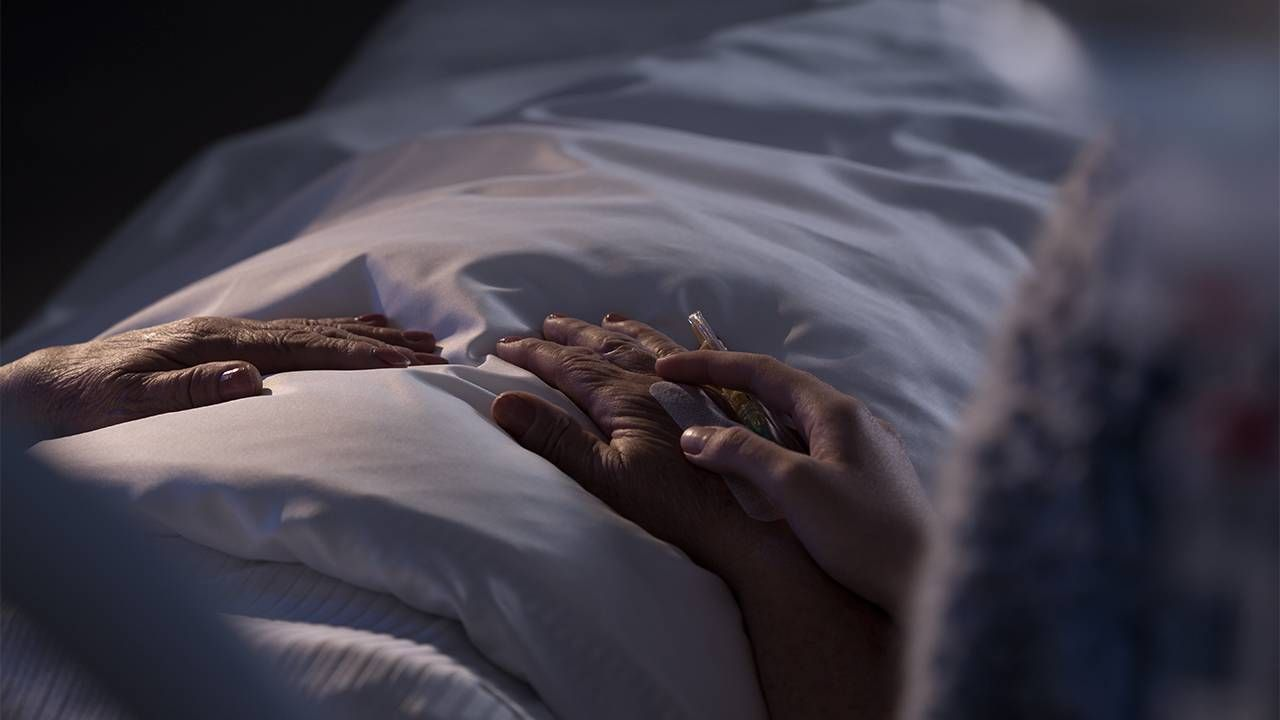 A hospice patient holding hand with a loved one. Next Avenue, hospice care