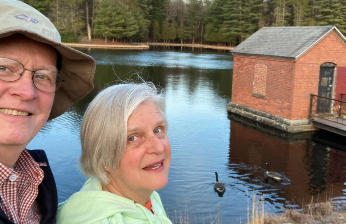 Lee and Linda Hilliard near a lake and evergreen trees. Next Avenue, climate change, stock, investments, green investing