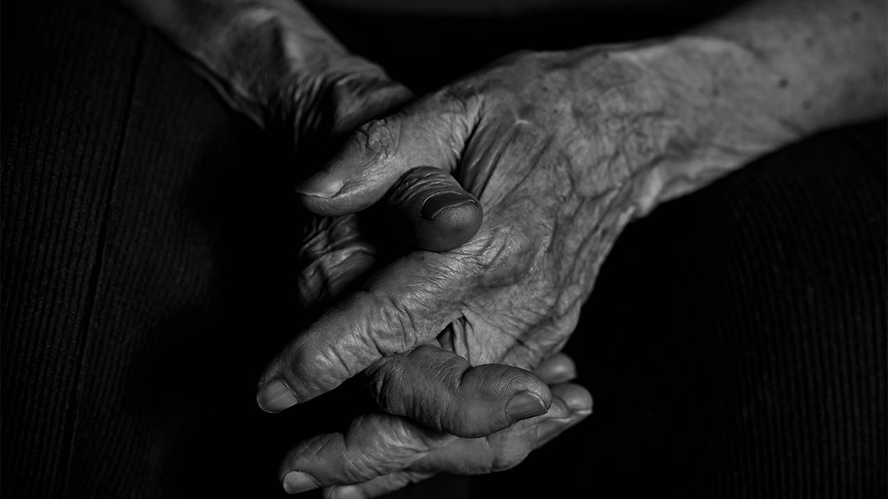 A close up shot of hands clasped in black and white. Next Avenue, isolation, loneliness, end of life