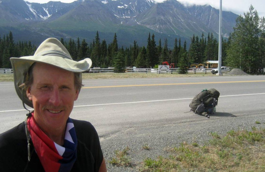 Michael Sean Comerford standing on the side of the road with a backpack. Next Avenue, route 66, carnival