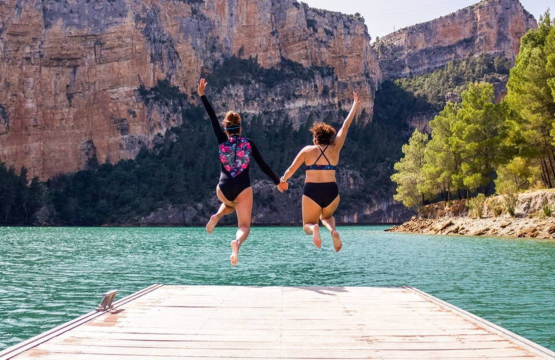 Two friends jumping off the end of a dock. Next Avenue, take a leap