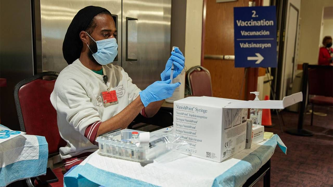 A health care provider prepping COVID-19 vaccines at a pop-up clinic. Next Avenue