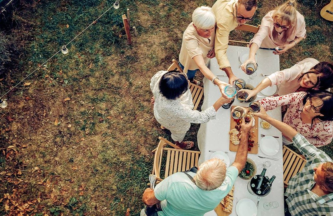 Aerial view of a group of friends eating a meal outside. Next Avenue, well-being, new normal