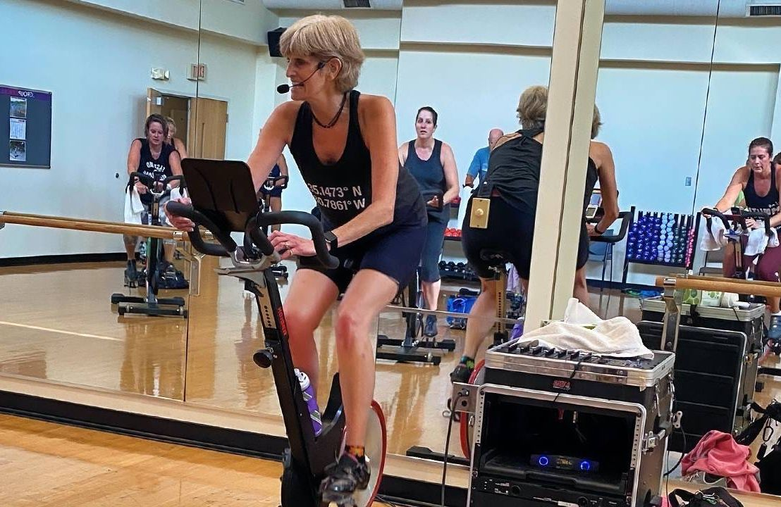 An older fitness trainer teaching a cycling class. Next Avenue