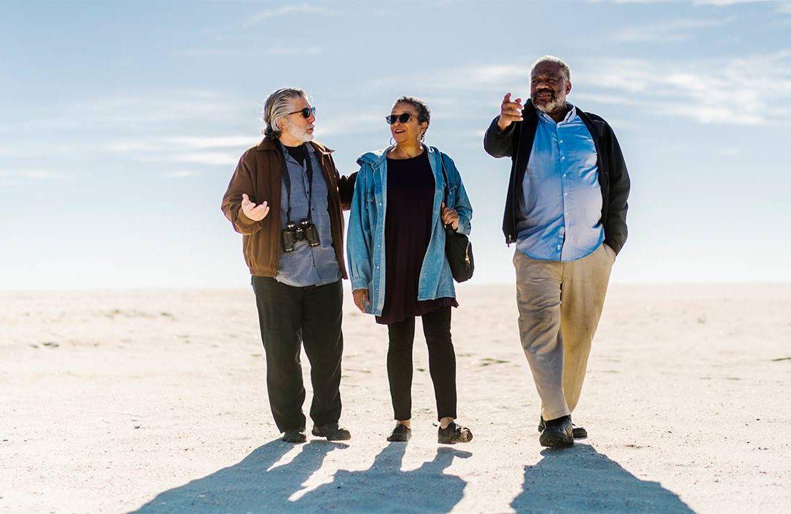 A group of older adult friends walking on beach. Steven Petrow, Next Avenue