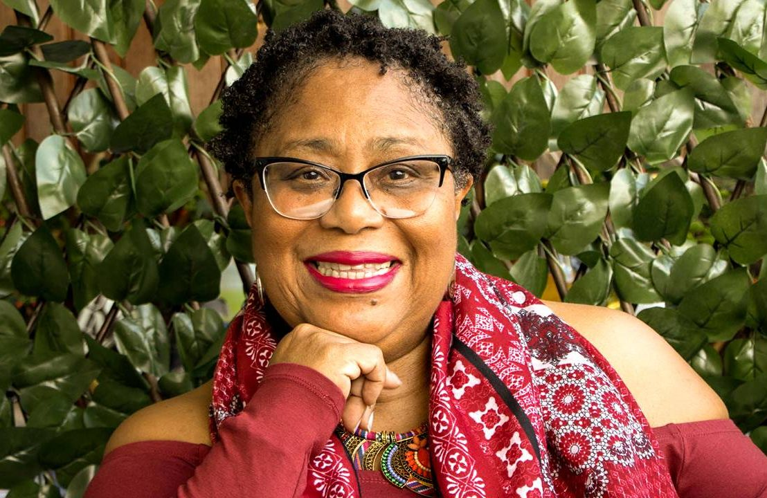 Author Dahlma Llanos-Figueroa wearing a red shirt and scarf. Next Avenue, Daughters of the Stone, afro-latina author