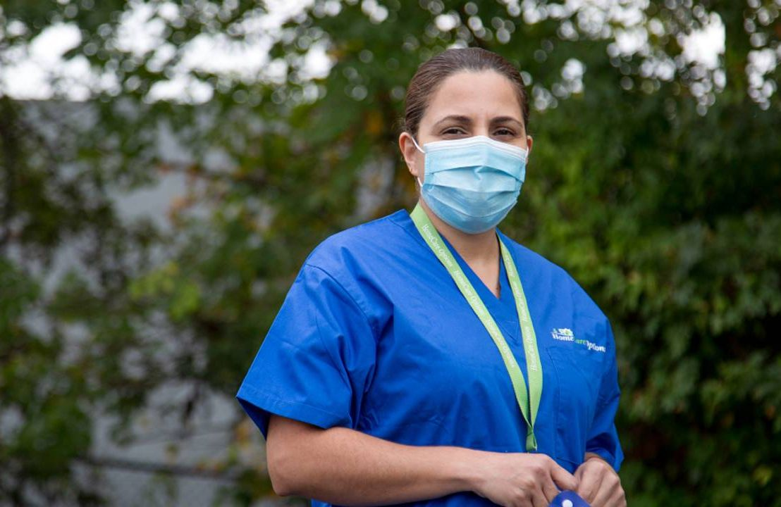 A woman standing in a parking lot wearing scrubs and a face mask. Next Avenue, paid caregivers, CNAs, caregiving work