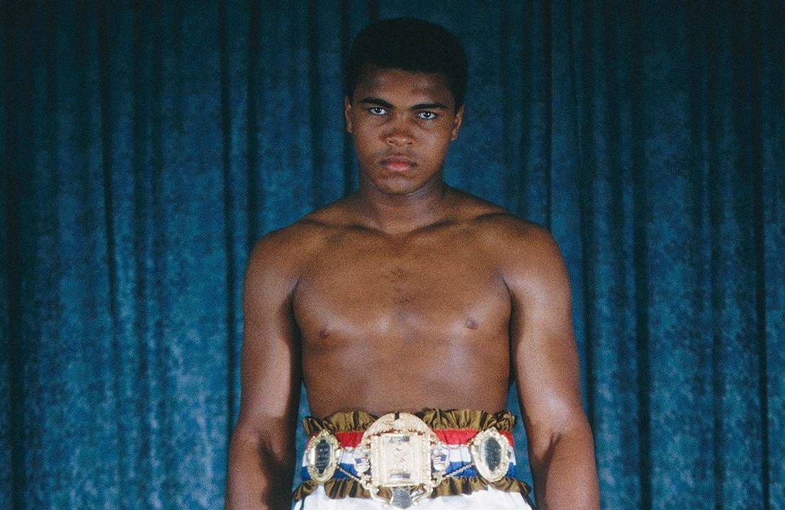 A young Muhammad Ali wearing boxing shorts and a medal around his waist. Next Avenue, Muhammad Ali, PBS