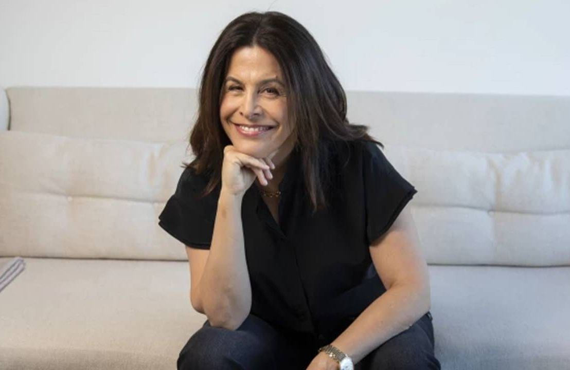 Amy Baer sitting on a white couch wearing black. Next Avenue, film company, Landline Pictures, 50, fifty