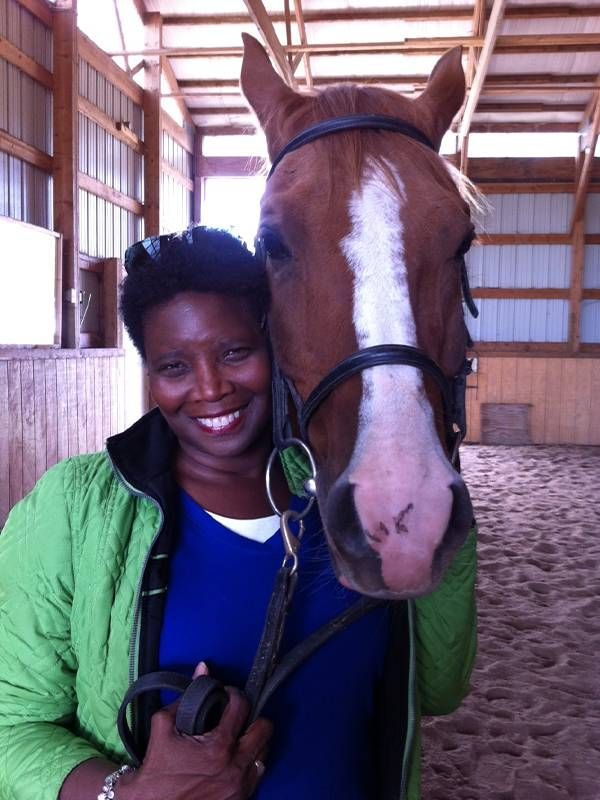 A woman standing cheek-to-cheek with a horse in a barn.Next Avenue, nonprofit jobs work, corporate