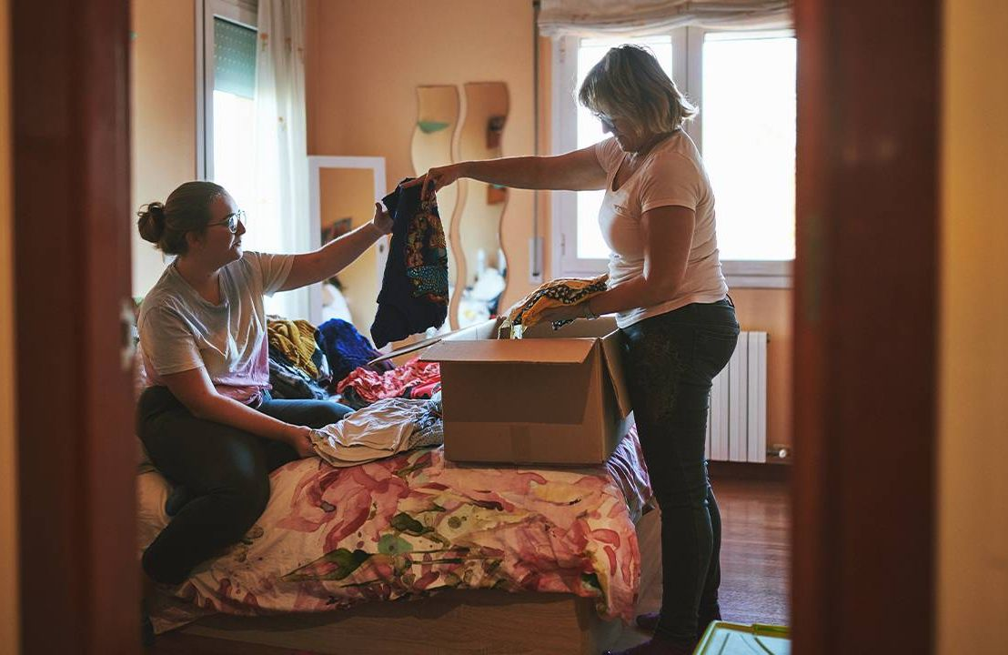A mother and daughter sorting through clothes. Next Avenue, clothing donation, recycled clothing