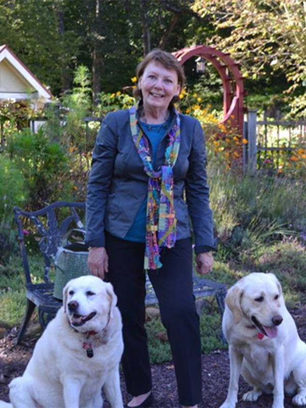 The author smiling while walking her dogs. Next Avenue, happy at work