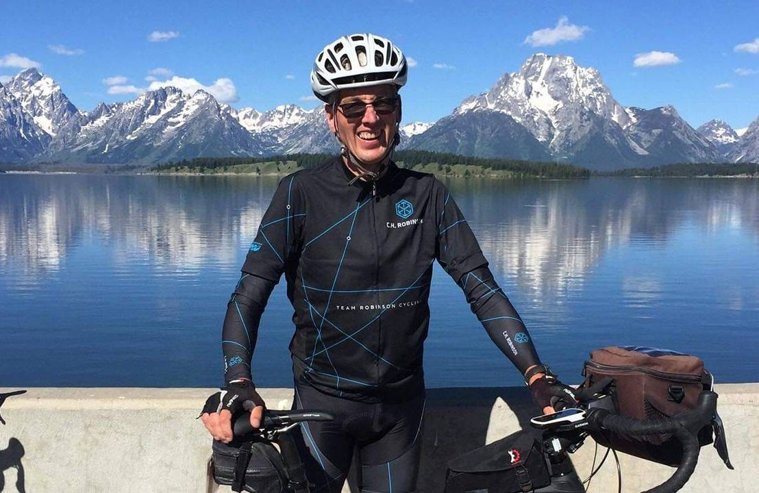 A man standing in front of a mountain range wearing a helmet and holding his bike. Next Avenue, cycling, biking, bicycling