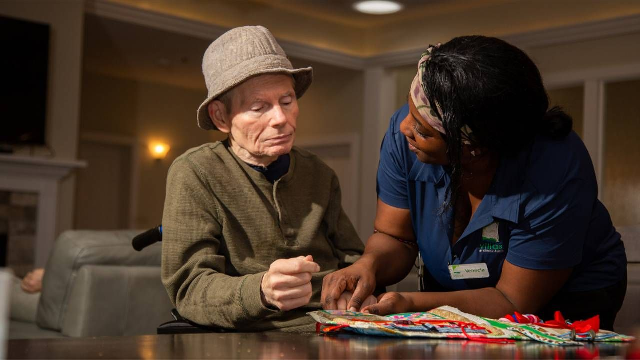 A woman wearing scrubs helps an older man in a wheelchair. Next Avenue, paid caregivers, CNAs, caregiving
