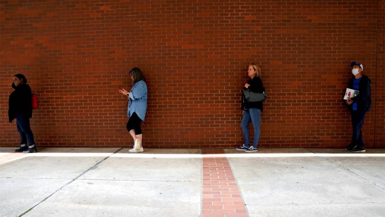 People lined up outside a brick building for unemployment. Next Avenue, laid off, lay-offs
