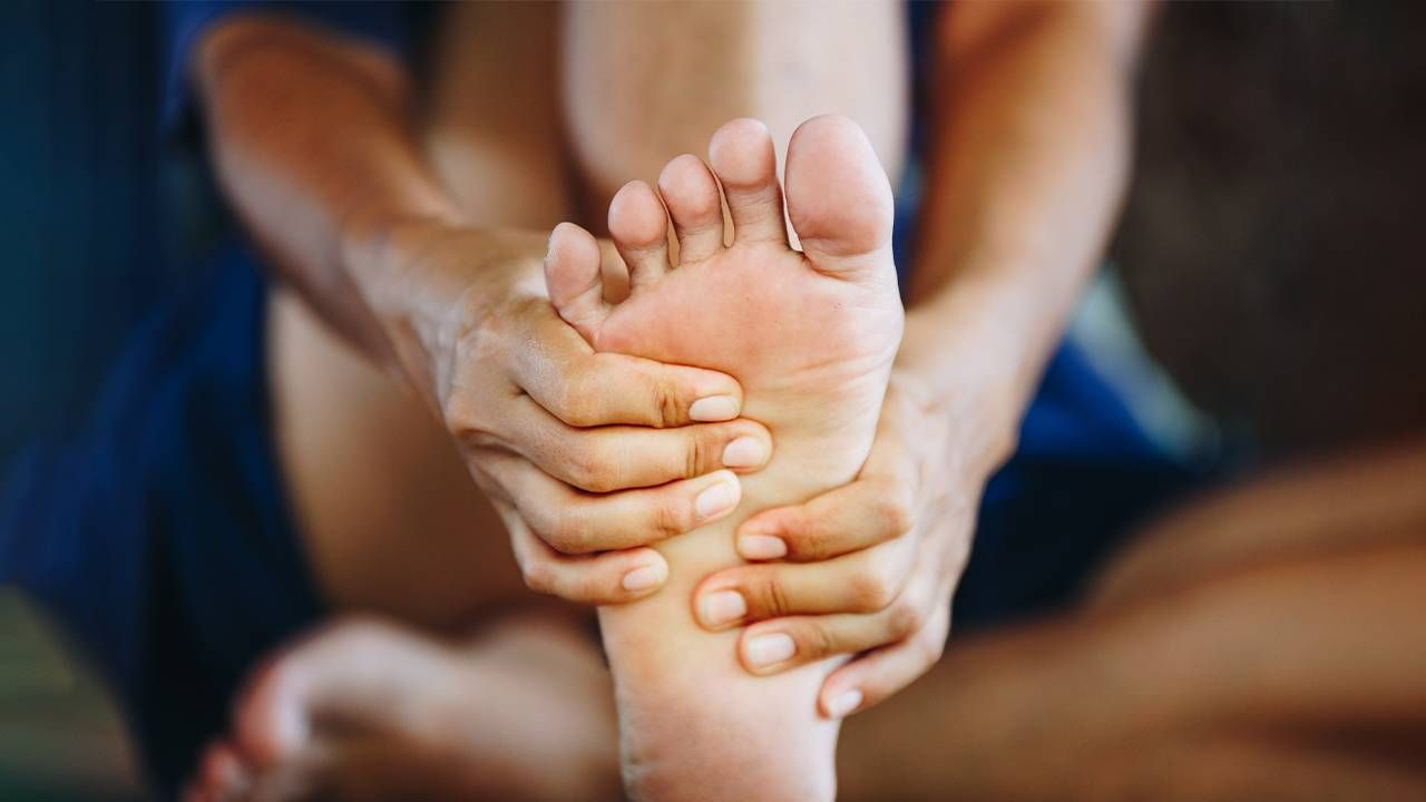 A person rubbing their foot. Next Avenue, foot pain
