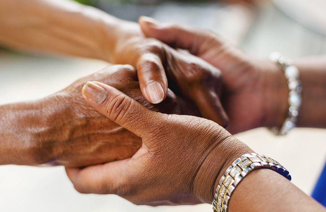An adult caregiver holding her mother's hands. Next Avenue, paid family leave, family caregiving