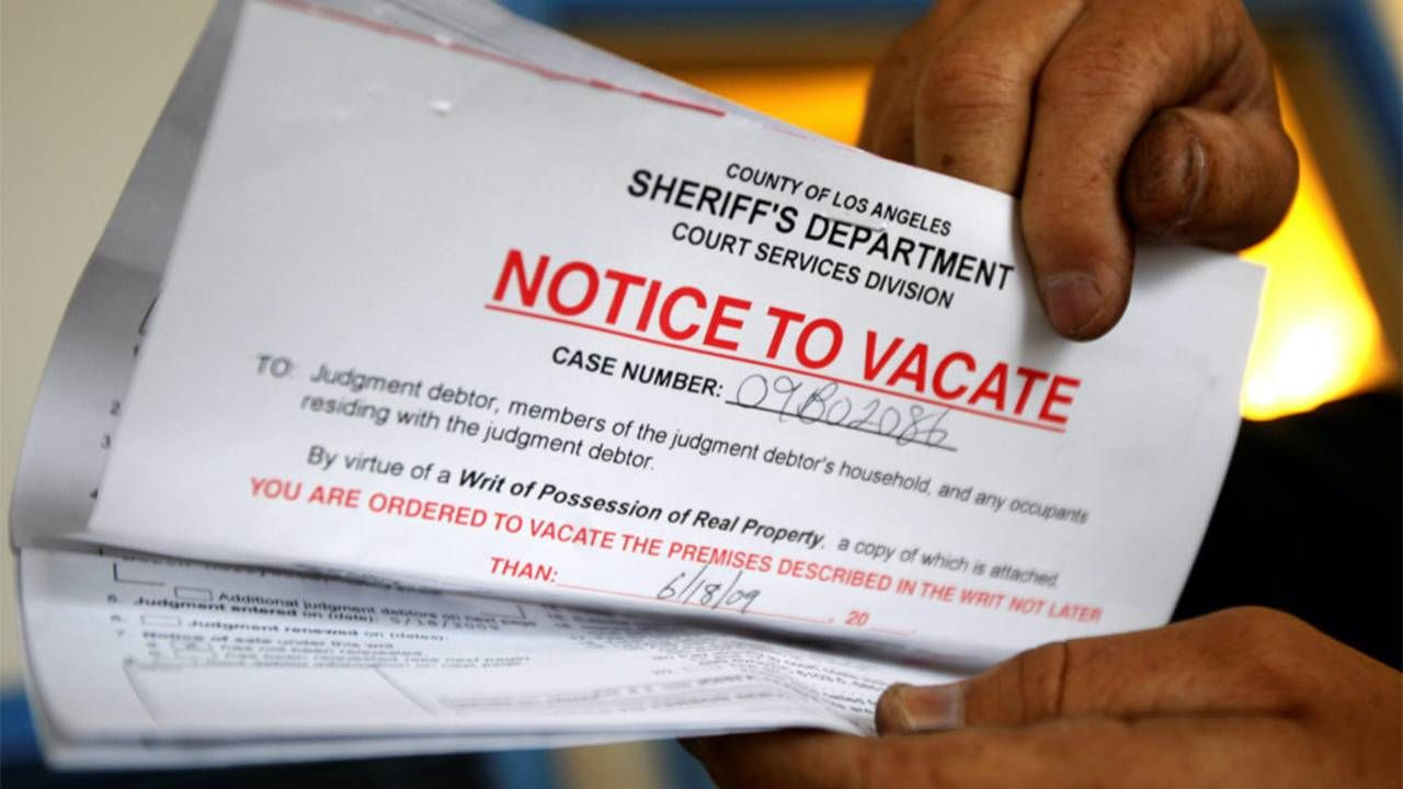 """A person holding up a """"Notice to vacate"""" paper. Next Avenue, eviction moratorium, senior homelessness"""