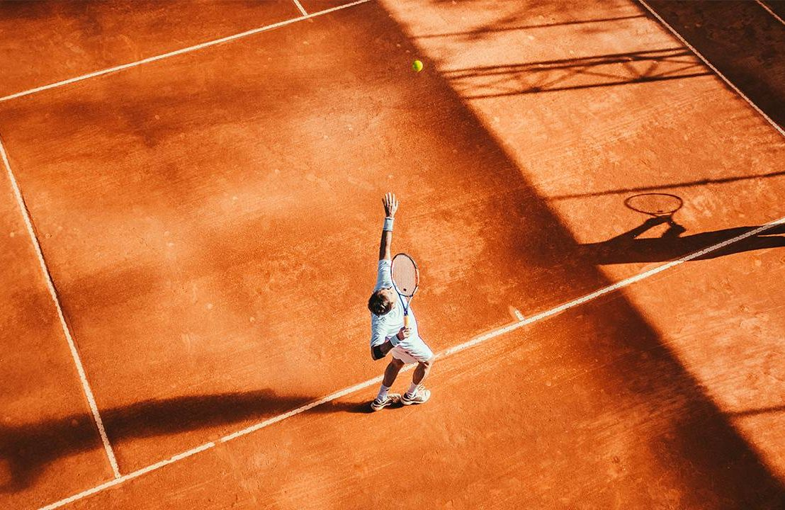 A man playing tennis on a clay court. Next Avenue