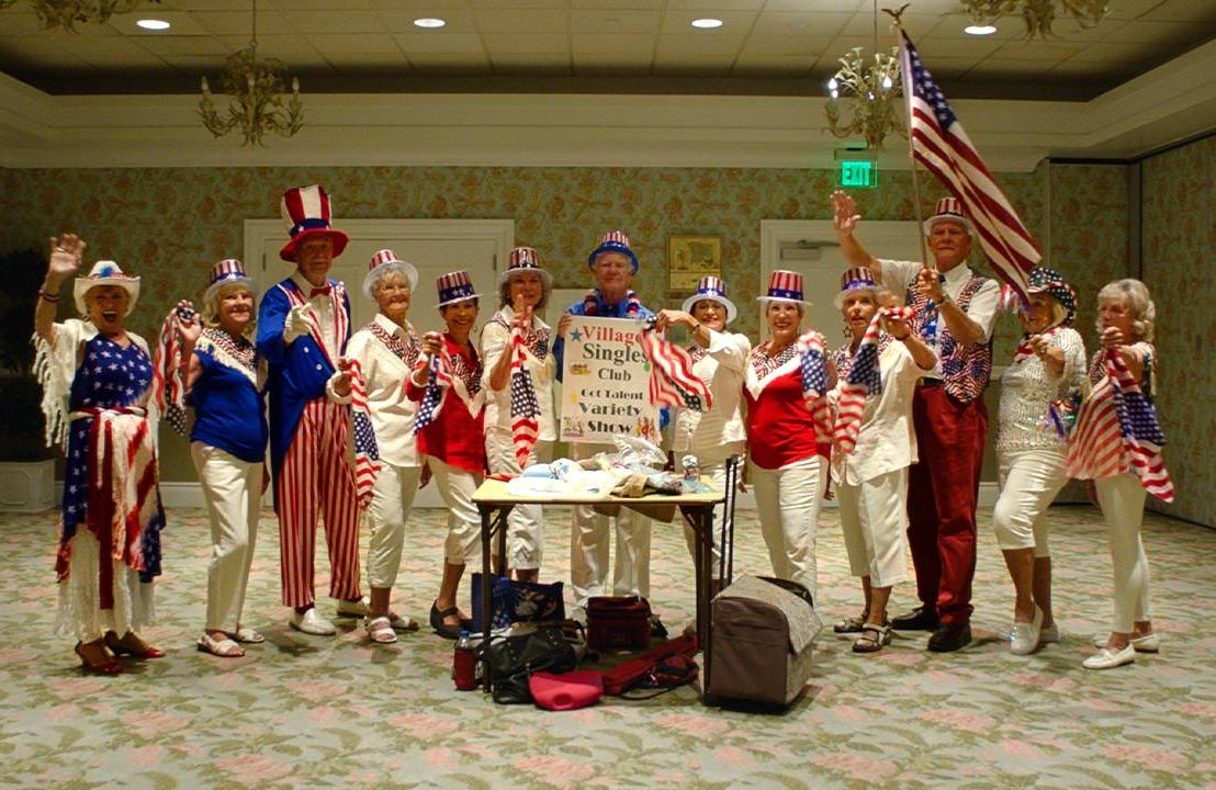 A group of older adults wearing patriotic clothing waving. Next Avenue, The villages, retirement community, diversity, intergenerational
