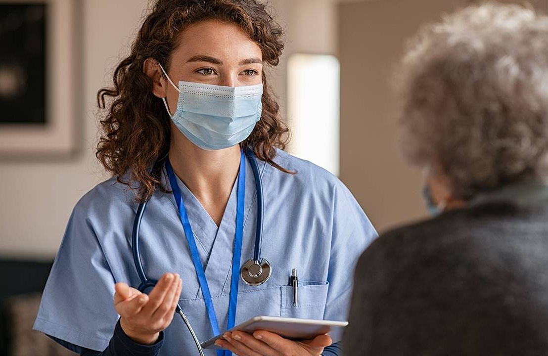 A nurse speaking to a nursing home resident and explaining something.