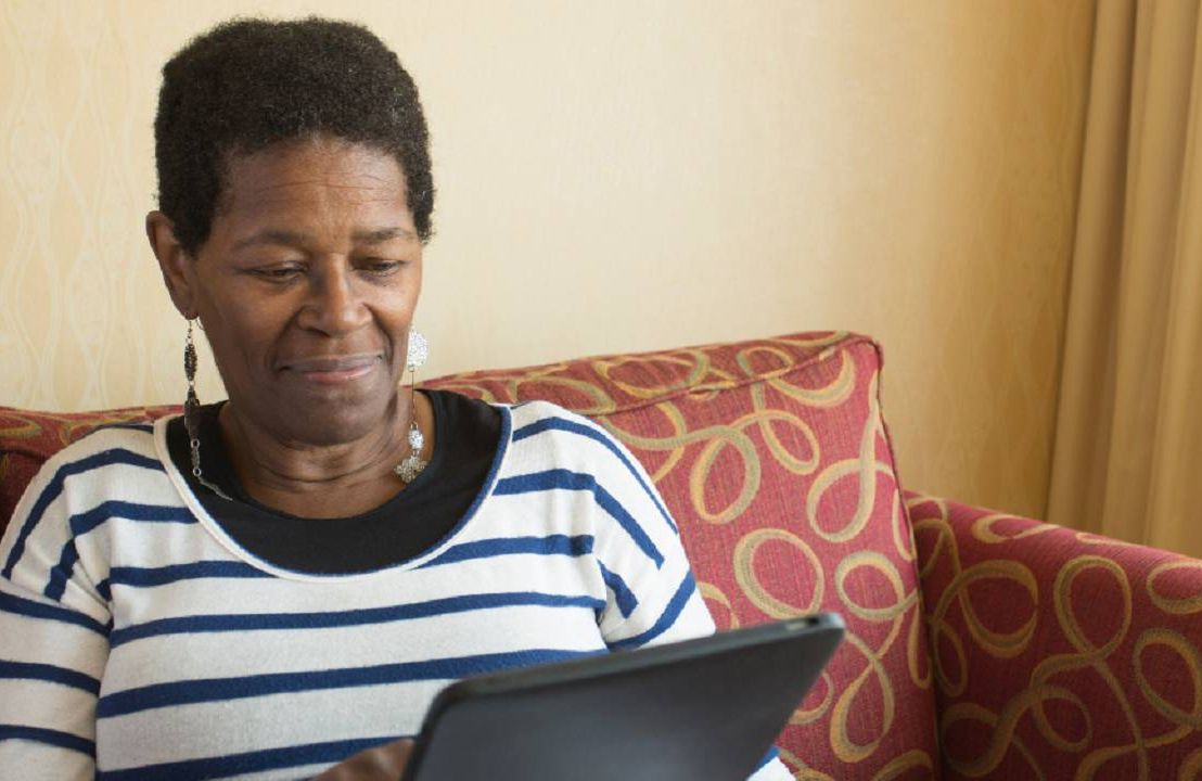 Older person sitting on a couch researching something on their tablet.