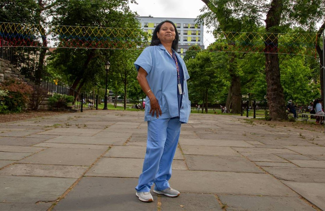 A person wearing scrubs standing in a park. Next Avenue, direct care workers, direct care workforce, staff shortages