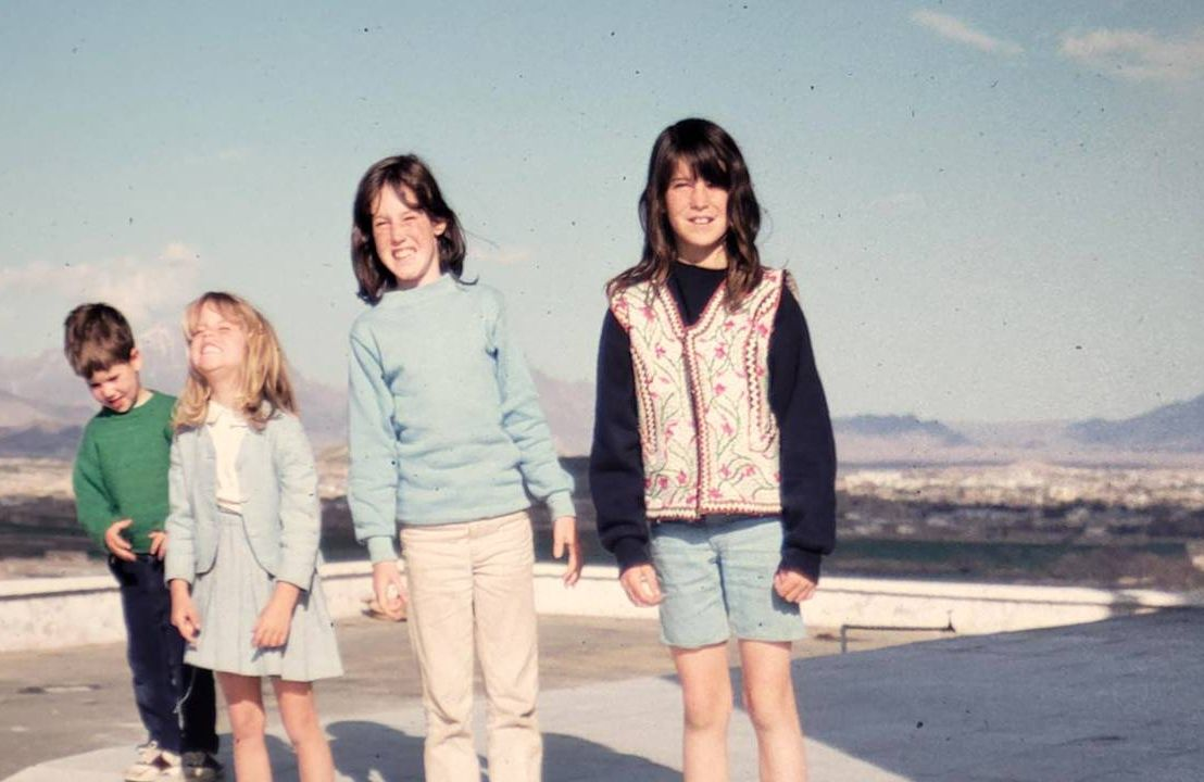 Four children smiling with a cityscape behind them. Next Avenue, Family trip, Afghanistan, Kabul