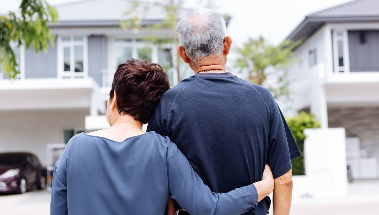 A couple standing in front of a new house. Next Avenue, relocating in retirement, where to live in retirement