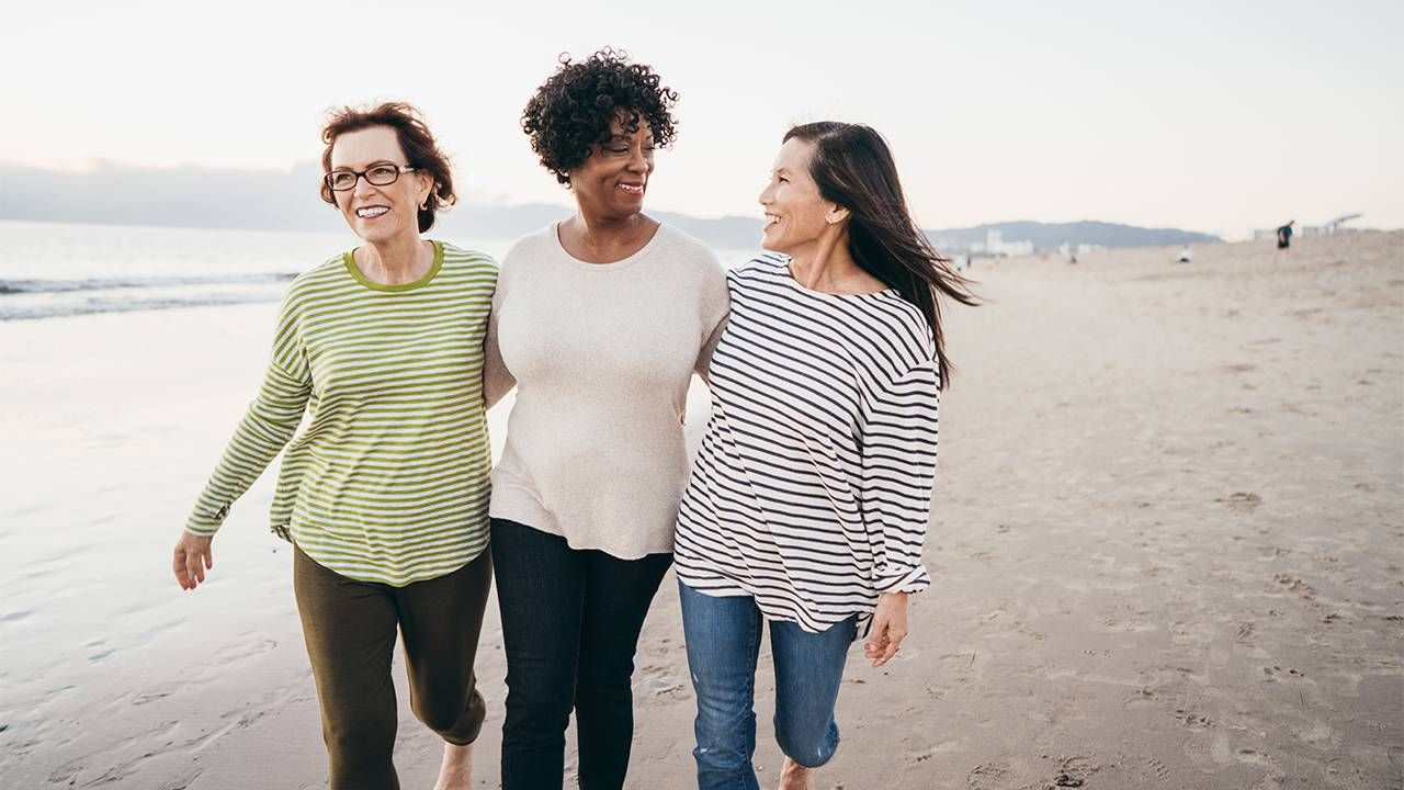 A group of friends walking on the beach. Next Avenue, menopause symtopms
