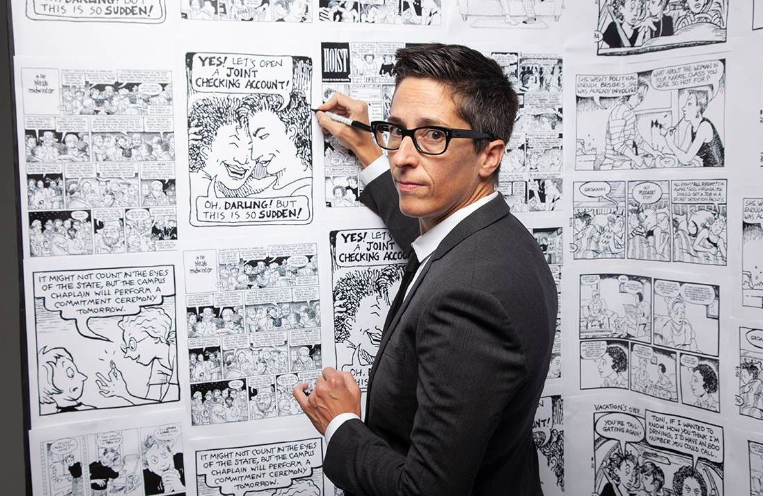 A comic artist drawing on a wall of comics. Next Avenue, queer comics, No Straight Lines