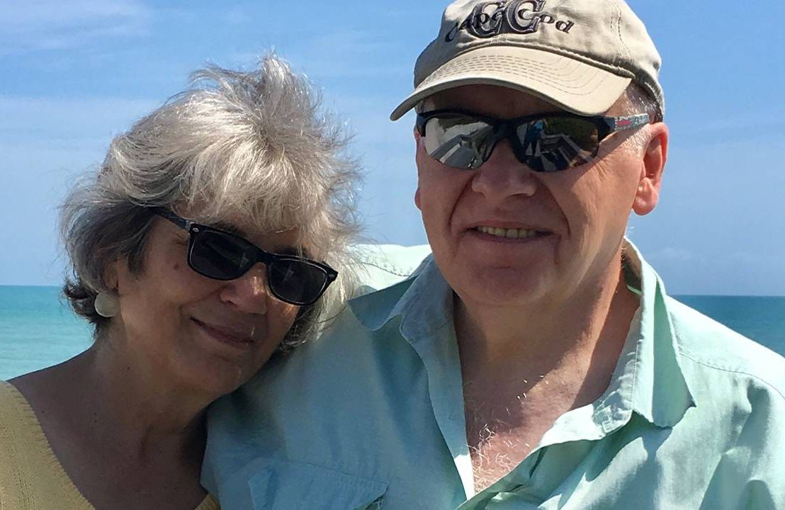 A couple smiling in front of the ocean. Next Avenue, retirement, retiring, on a budget