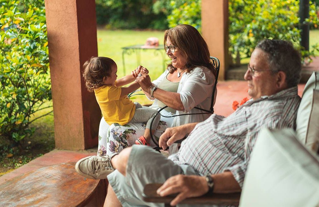 A couple sitting on the porch with their grandchild. Next Avenue, reverse mortgage