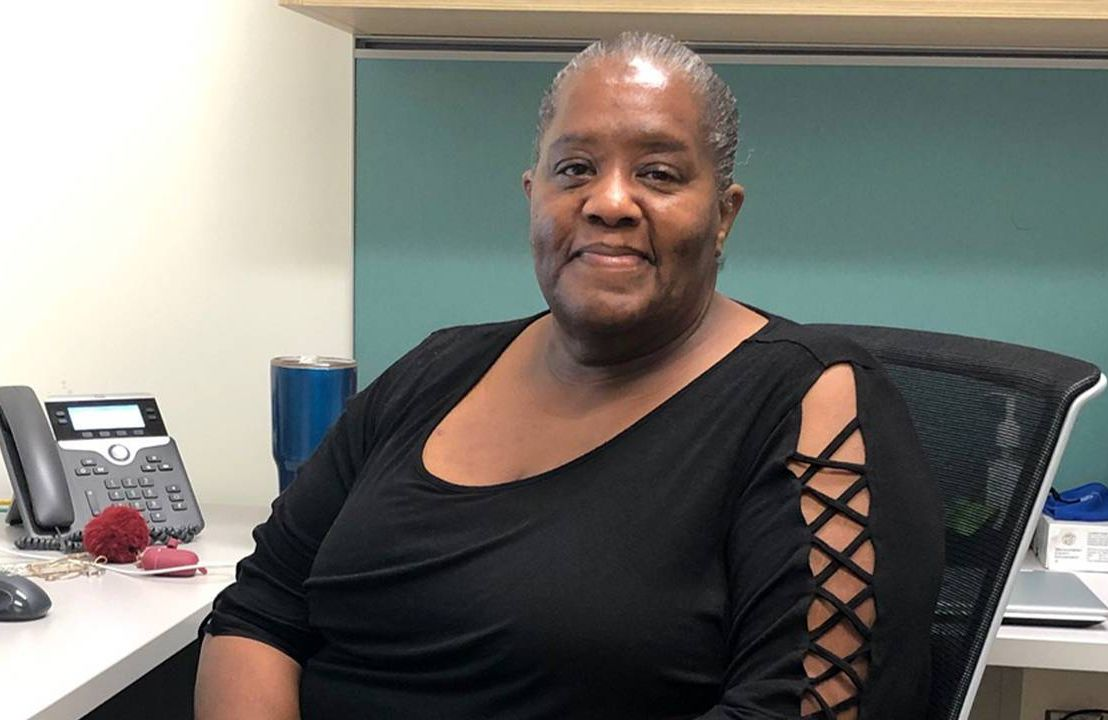 A person sitting in an office wearing a black shirt. Next Avenue, Black adults mental health, counseling