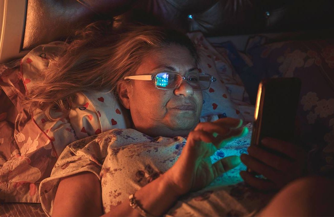 A woman laying in bed looking uncomfortable on her phone. Next Avenue, symptoms of perimenopause, what is perimenopause